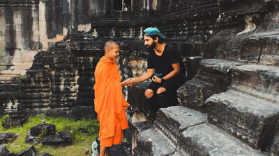 Racer sitting on some steps clasping hands with a monk who is praying over him