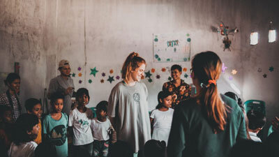 Woman in a classroom in Indonesia with children around her in a circle